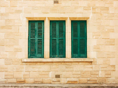 Green shutters on the old wall, made of stone in a row Stock Photo