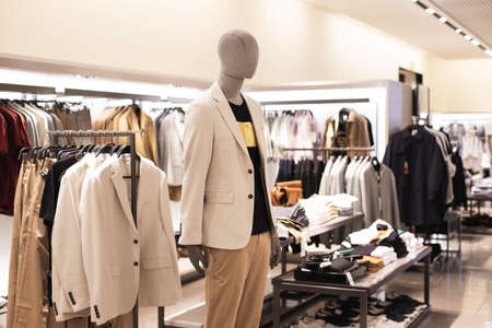 Mens clothing, fashionable, stylish on hangers in stores, a mannequin. A concept of shopping, Sales. Jacket beige, pastel colors