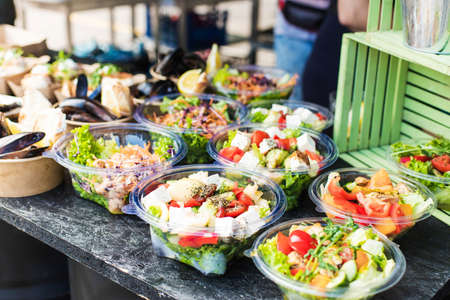 Vegetarian appetizing salads, mussels at a street festival Banque d'images - 132092291