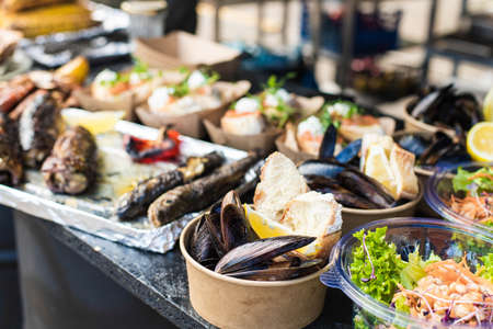 Appetizing fish, mussels, salmon, corn at a street festival Banque d'images - 132091827