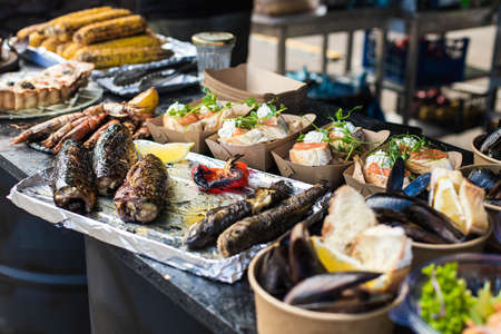 Appetizing fish, mussels, salmon, corn at a street festival Banque d'images - 132092124