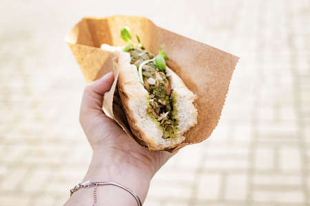 Vegan, vegetarian hot dog with soy sausage in female hand at a street festival Banque d'images - 132092476