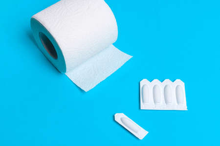 Medical suppository and toilet paper on a blue background, for the treatment of hemorrhoids, vaginal candidiasis