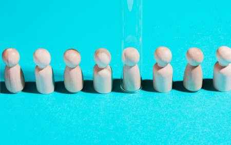 Baby birth concept with test tubes. Artificial insemination. Wooden figures under test tube on a blue background