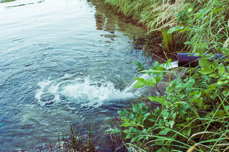 Sewage flows into the lake, river. Water flows from the pipes. Environmental pollution.