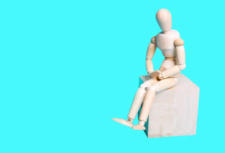 Wooden human figure on a blue background. The concept of pain in the abdomen, stomach, menstruation Reklamní fotografie