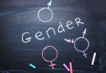 The word gender and symbols of man, woman, drawn in chalk on a blackboard