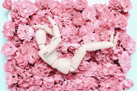 Wooden mannequin on a background of flowers. Depression concept,, sadness, problem