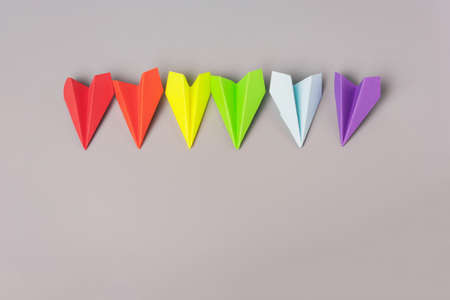 Paper airplanes of rainbow color, flag on a gray background