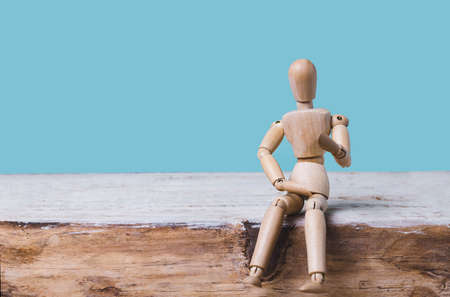Wooden man mannequin sits on blue background. Place for text .Concept of idea, creative, training