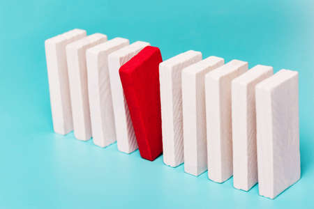 The concept of leadership, differences, inequality. Dominoes on blue background. Stock Photo