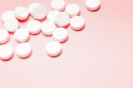 White, round pills on a pink background. The concept of the treatment of the disease, healthcare, women's health.