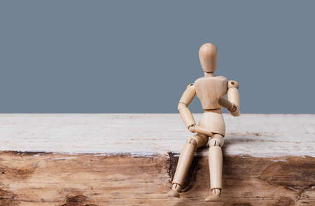 Wooden man dummy sits and speaks on a gray background. Place for text .Concept of idea, creative, training, education