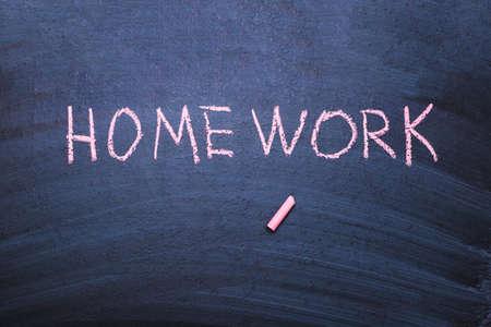 The word homework is written in chalk on a blackboard. Stock Photo