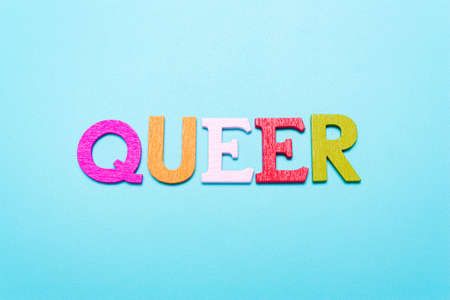QUEER word from rainbow color letters on  blue