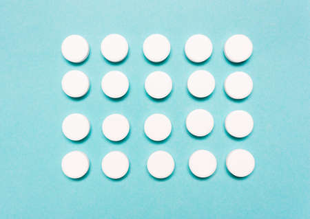 Round, white pills on a blue background. The concept of the treatment of the disease, healthcare, pharmaceuticals. Stock Photo