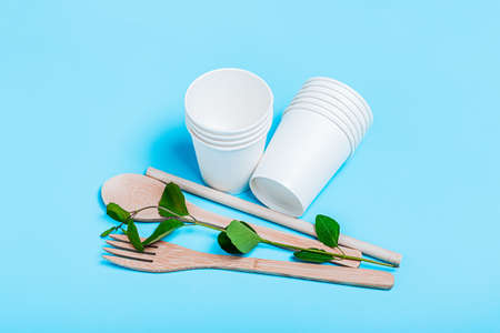 Organic fork, spoon, wooden tube, paper cups on a blue background. The concept of recycling, eco, planet conservation, zero waste