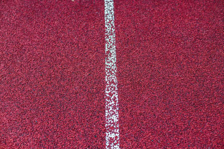 Background of red treadmill, stadium. White lines, stripes