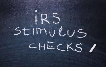 Irs stimulus checks is written in chalk on a blackboard.