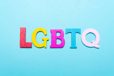 LGBTQ word from rainbow color letters on a blue background Standard-Bild