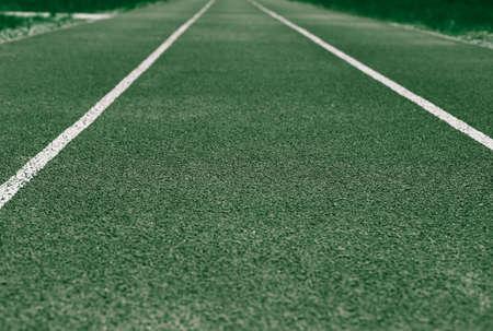 Background of green treadmill, stadium. White lines, stripes