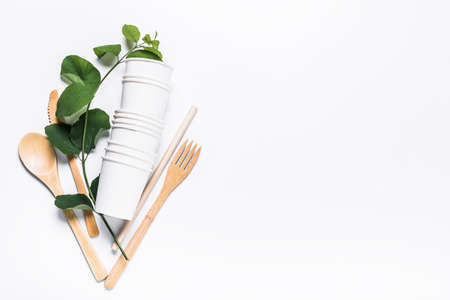 Paper cups, wooden fork, spoon, knife, tube, on white background. The concept of recycling, ecology, planet conservation, zero waste