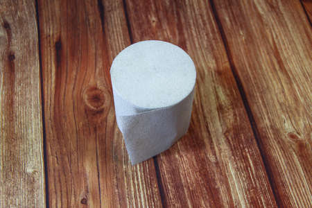 Roll of toilet paper on the wooden background, top view