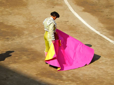 capote: Bullfighter in the ring. brave matador with capote. dress in green
