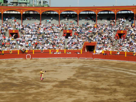 capote: Brave matador salutes the audience in the middle of the arena. bullfighting