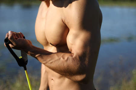 muscular super-high level man pulls rubber bands. outdoors photo