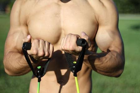 hombre muscular super-alto nivel saca bandas de goma. al aire libre photo