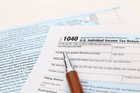 1040 Income tax form and pen. Finance concept. over a white background Banco de Imagens