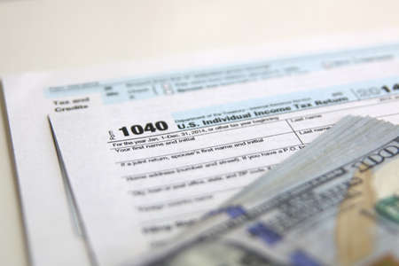 taxable: USA Tax Form 1040 with 100 US dollar bills. business concept