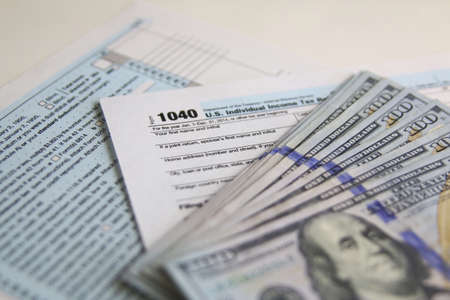 taxable: US Tax Form 1040 with new 100 US dollar bills. business concept Stock Photo