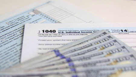 federal: USA Tax Form 1040 with 100 US dollar bills. business concept