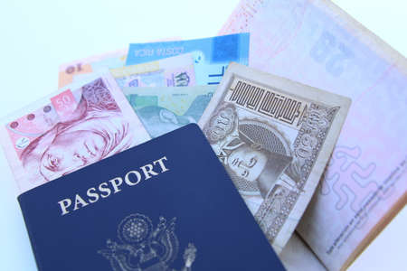 USA passport and international currencies on a white background