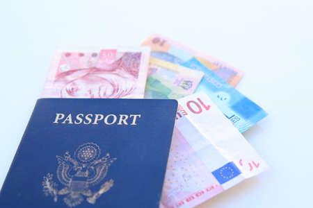 Pasaporte americano y monedas multinacionales sobre un fondo blanco Foto de archivo - 36889213