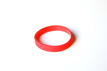red rubber bracelet isolated over a white background