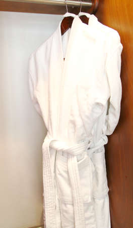 clean clothes: luxury white bathrobes hanging in wooden closet