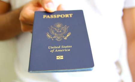白で隔離される米国からのパスポートを持っている手 写真素材