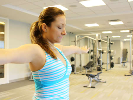 meditates: Portrait of pretty young woman doing yoga exercise in gym. The young girl meditates in a gym.
