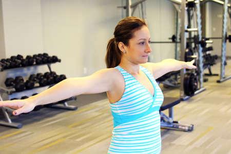 warm up: donna allungando le braccia per riscaldarsi. Palestra
