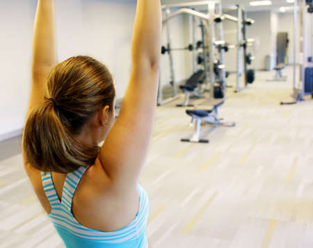 Female in gym class, relaxation exercise or yoga class. The young girl meditates in a gym.
