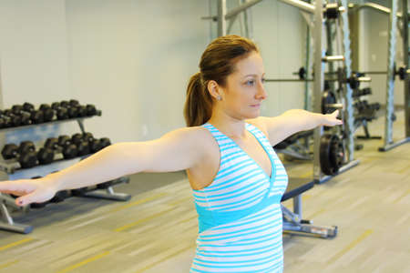 warm up: woman stretching her arms to warm up. Gym