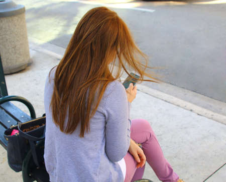 distance: Casual woman waiting for public transportation and checking her phone. sunny day