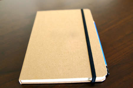 reading materials: light brown notepad book and pencil over a table