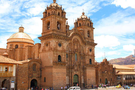 la compania: Twin towers and dome of the historic Iglesia de la Compania seen across the red rooftops of Cusco in Peru. The church dates back to 1571 and sits on top of an old Inca Palace.