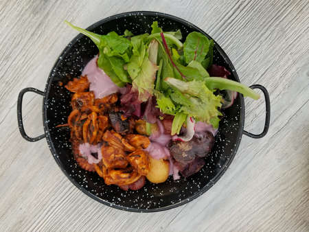 Octopus grilled: Peruvian dish served with fresh salad over a white reclaimed wood table