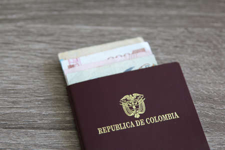 Colombian passport with bank notes over a light grey wooden background Stock Photo