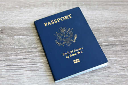 US passport over a light grey wooden background